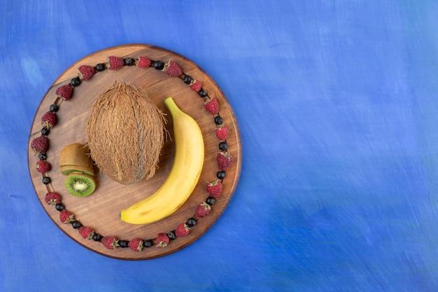 Ein holzbrett aus kokosnuss, kiwi und banane