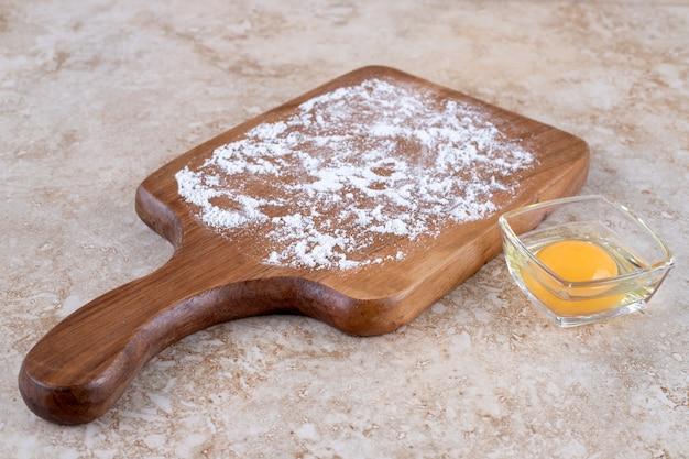 Ein holzbrett aus mehl und rohem eigelb