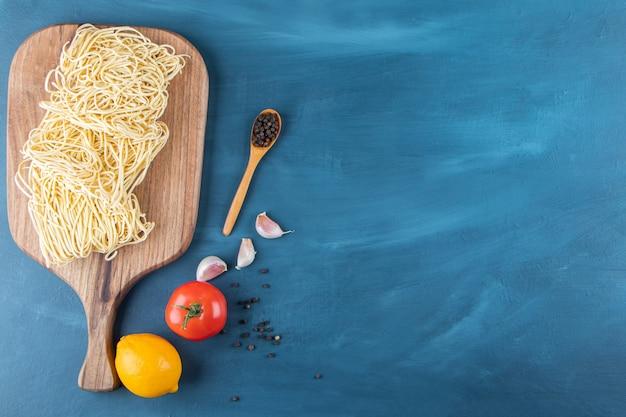 Ein holzbrett aus rohen nudeln mit frischen roten tomaten und zitrone auf blauem hintergrund..