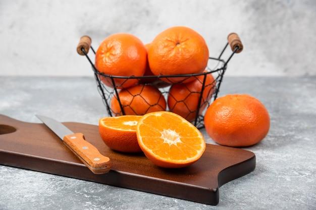 Ein holzbrett aus saftigen orangenfruchtscheiben mit einem messer auf steintisch.