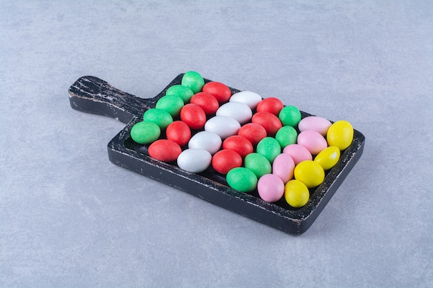 Ein holzbrett mit bunten süßen jelly bean bonbons. foto in hoher qualität