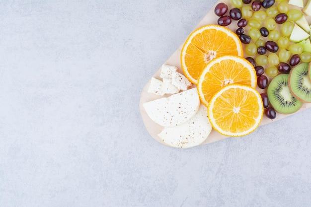 Ein holzbrett mit frischen früchten auf weißem hintergrund. foto in hoher qualität