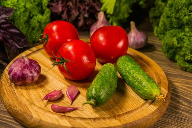 Ein holzbrett mit frischen tomaten gurken und knoblauch. zusammensetzung mit frischem gemüse