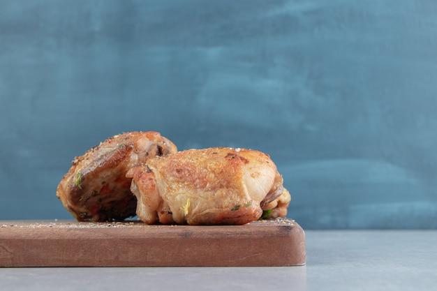 Ein holzbrett mit gebratenem hühnerfleisch mit genuss.