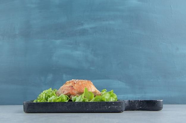 Ein holzbrett mit gebratenen hühnerbeinen und salatsalat.