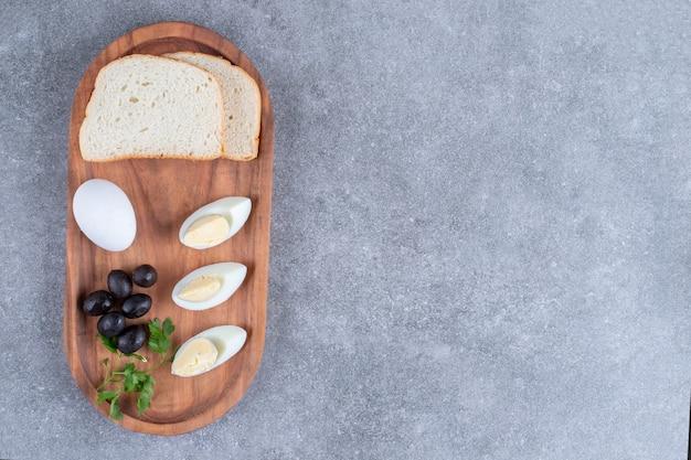 Ein holzbrett mit gekochtem ei und brotscheiben