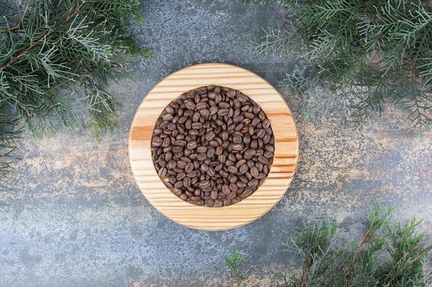Ein holzbrett mit kaffeebohnen auf marmorhintergrund. foto in hoher qualität
