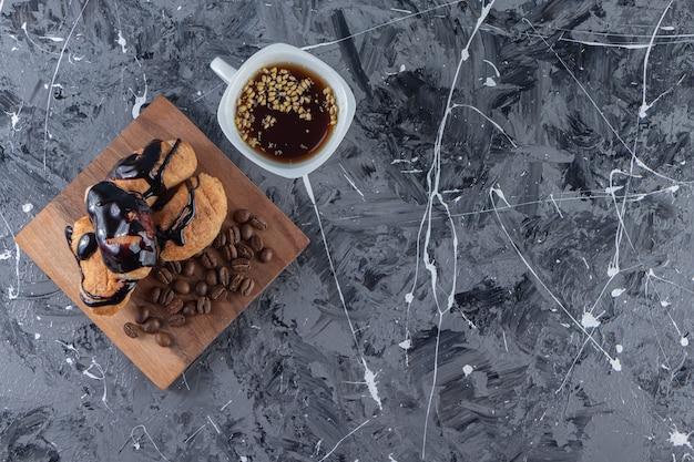 Ein holzbrett mit mini-croissants mit schokolade und kaffeebohnen.