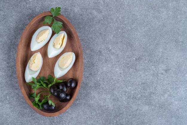 Ein holzbrett mit oliven und gekochten eiern. hochwertiges foto