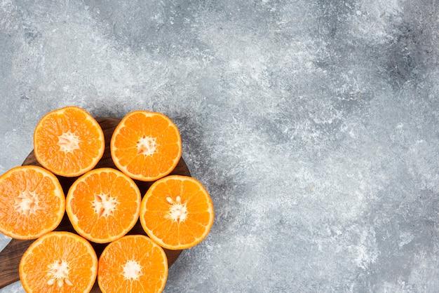 Ein holzbrett mit saftigen orangenfruchtscheiben auf steintisch.