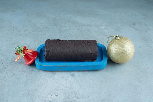 Ein holzbrett mit schokoladenkuchenrolle mit weihnachtsspielzeug.