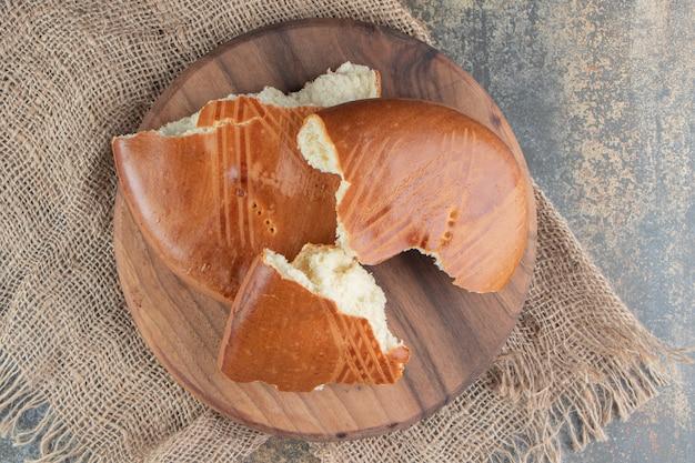 Ein holzbrett mit süßem, köstlichem gebäck auf einem sack