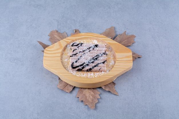 Ein holzbrett mit süßen leckeren sticks mit schokoladensirup