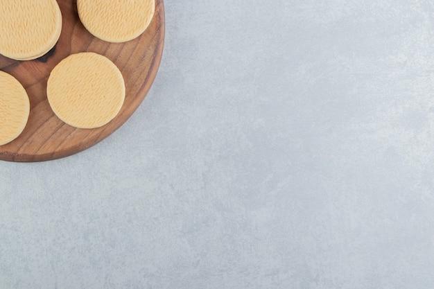 Ein holzbrett mit süßen runden keksen.