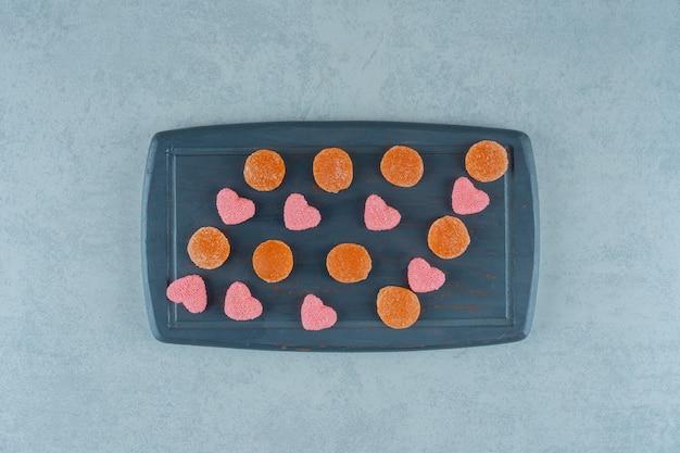 Ein holzbrett voller orangefarbener zuckerhaltiger geleebonbons mit herzförmigen geleebonbons