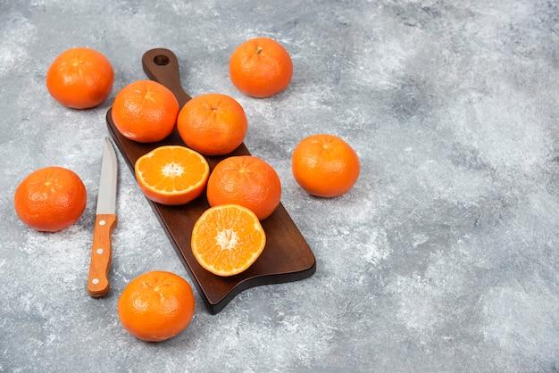 Ein holzbrett voller saftiger orangenfrüchte mit scheiben und einem messer auf steintisch.