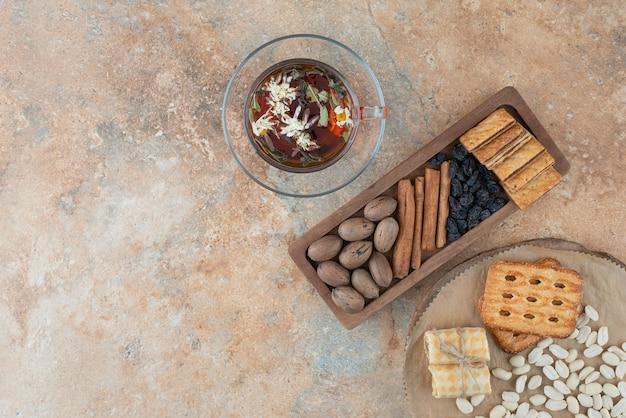 Ein holzbrett voller süßer kekse und einer tasse kräutertee