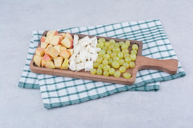 Ein holzbrett voller weißkäse und geschnittenen früchten. foto in hoher qualität