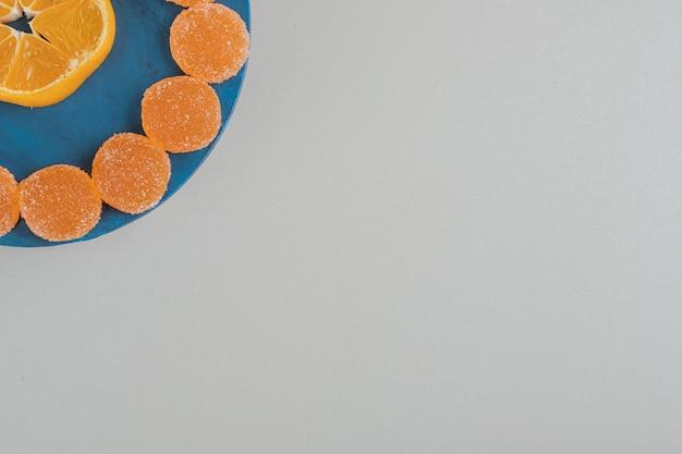 Ein holzbrett voller zuckerhaltiger geleesüßigkeiten und einer orangenscheibe.
