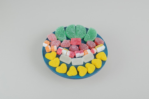 Ein holzbrett voller zuckerhaltiger geleesüßigkeiten.