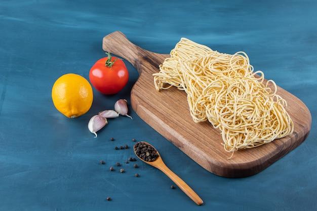 Ein holzbrett von rohen nudeln mit frischer roter tomate und zitrone auf einem blauen hintergrund.