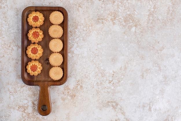 Ein holzbrett von süßen keksen mit streuseln im loch auf einem steintisch.