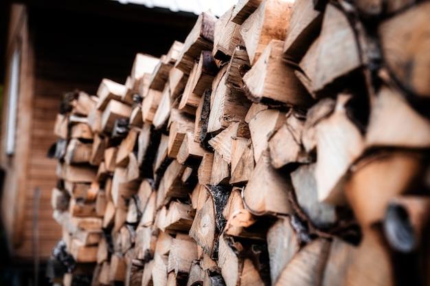 Ein holzhaufen mit ernte und gestapeltem brennholz aus gehacktem holz zum anzünden und heizen des hauses. brennholz der birke