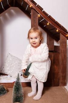 Ein holzhaus. ein glückliches kind spielt mit spielzeug, künstlichen kleinen weihnachtsbäumen.
