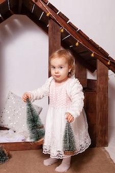 Ein holzhaus. ein kind spielt mit spielzeug, künstlichen kleinen weihnachtsbäumen.