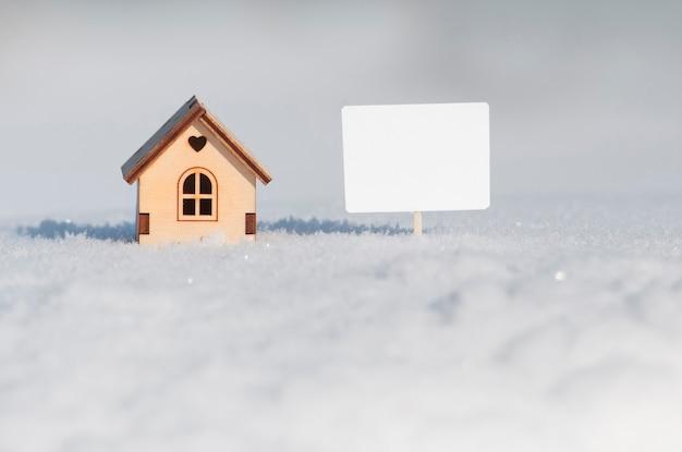 Ein holzhaus mit einem herzen und einem weißen leeren schild daneben in der schnee-nahaufnahme.