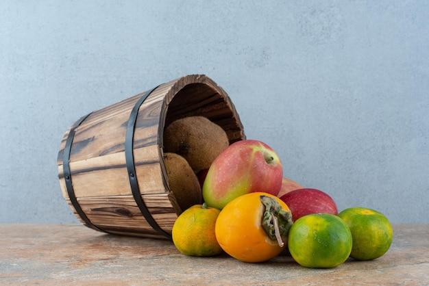Ein holzkorb mit frischen süßen früchten auf grau