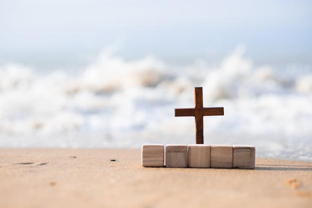 Ein holzkreuz im sand am strand.
