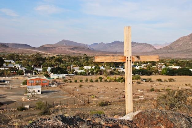 Ein holzkreuz mit blick auf die stadt prince albert in südafrika