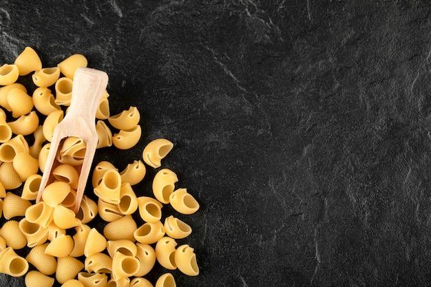 Ein holzlöffel ungekochte conchiglie-makkaroni.