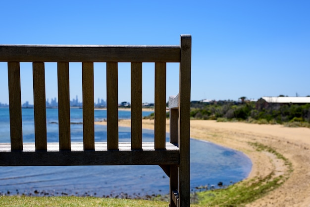Ein holzstuhl am strand mit stadtansicht als hintergrund.