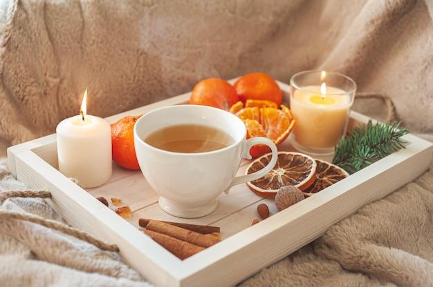 Ein holztablett mit tee, mandarinen, nüssen und gewürzen auf einem beigen plaid. winterfrühstück. das konzept der hygge. hochwertiges foto