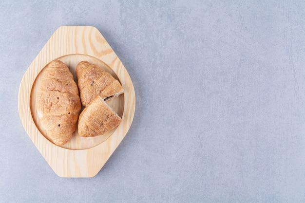 Ein holzteller mit croissants und leckerer schokolade.
