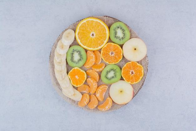Ein holzteller mit geschnittenen früchten auf weißem hintergrund. foto in hoher qualität