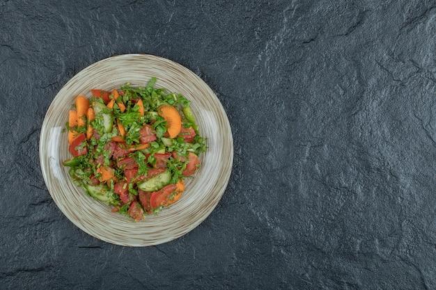 Ein holzteller mit köstlichem gemüsesalat.
