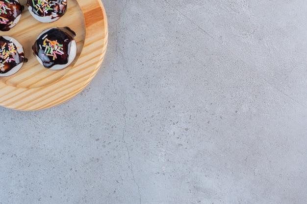Ein holzteller mit leckeren glasierten keksen auf steinhintergrund.