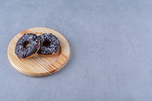 Ein holzteller mit leckeren schokoladenkrapfen mit streuseln