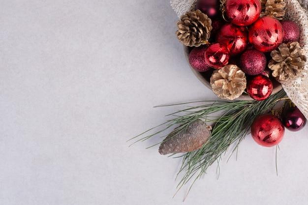 Ein holzteller mit roten weihnachtskugeln und tannenzapfen auf sackleinen