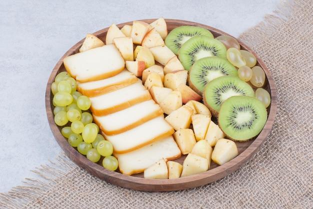 Ein holzteller voller geschnittener früchte und brot. foto in hoher qualität