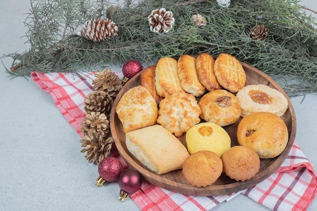 Ein holzteller voller süßem gebäck mit weihnachtskugeln und tannenzapfen