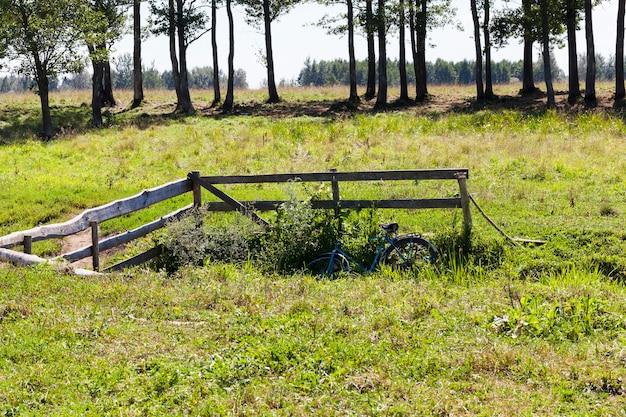 Ein holzzaun in der nähe der brücke über den bach, dorflandschaften im sommer, in der nähe des zauns gibt es ein fahrrad, auf dem menschen zur ruhe kamen
