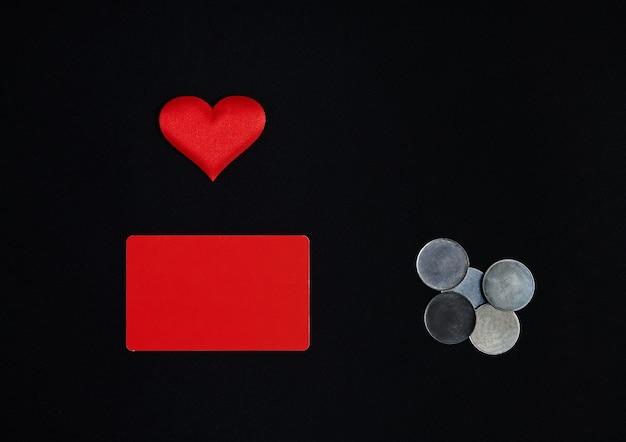 Ein horizontales rotes rechteck, ein rotes herz und geldmünzen auf einem schwarzen hintergrund. grenze, kopierraum, draufsicht, feier, feiertag