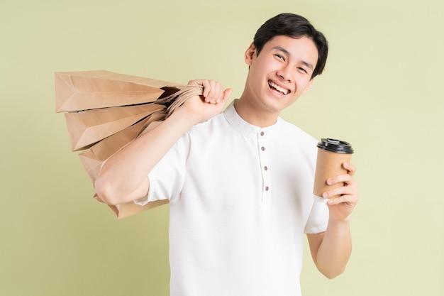 Ein hübscher asiatischer mann, der einkaufstaschen und eine tasse kaffee hält, um wegzunehmen