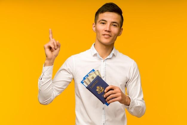 Ein hübscher asiatischer mann in einem weißen hemd freut sich über den gewinn der lotterie. er zeigt nach oben und hält einen pass mit flugtickets und gelddollar auf einem gelben platz.