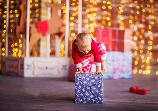 Ein hübscher blonder junge im weihnachtspyjama sitzt auf einer geschenkbox. weihnachten hintergrund. foto in hoher qualität