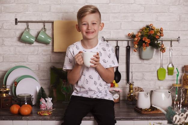Ein hübscher blonder junge sitzt mit einer großen weißen tasse in der hand auf dem küchentisch. lustiges foto